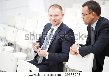 Two businessmen sitting on chairs of conference hall and working with touchpad