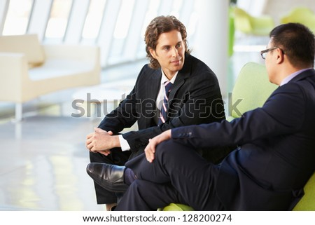 Two Businessmen Sitting On Sofa In Modern Office - stock photo