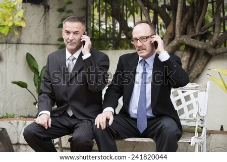 two businessmen sitting outside on a bench and talking on the phone