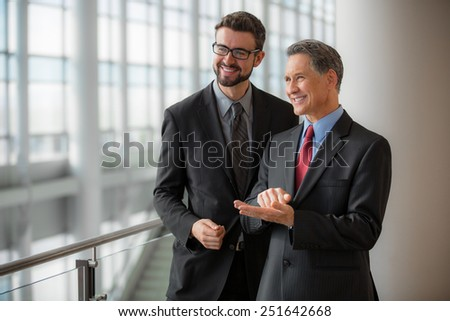 Two businessmen smiling at the office - stock photo