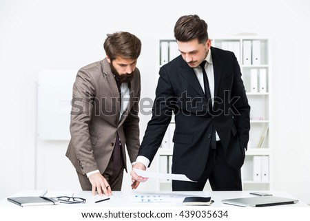 Two businessmen standing and doing paperwork at modern office desk. Concept of teamwork - stock photo