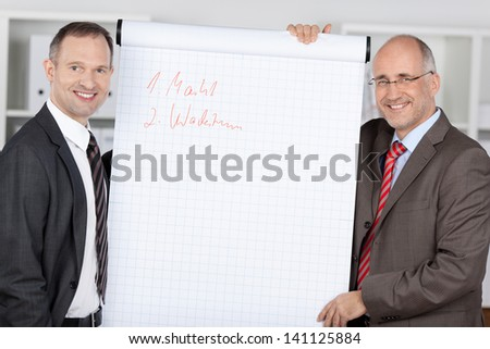 Two businessmen standing and present flipchart during business meeting - stock photo