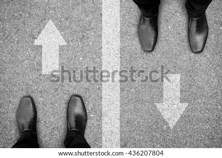 Two businessmen standing on different side of the road. Representing rivals, enemies, competitors in business and life. - stock photo