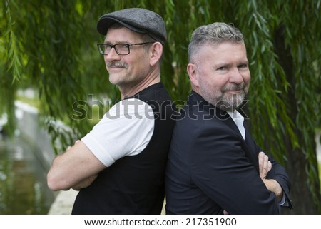 two businessmen standing together in a park and smiling