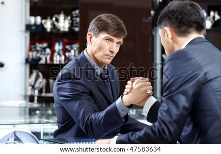 Two businessmen struggle on a forward background - stock photo