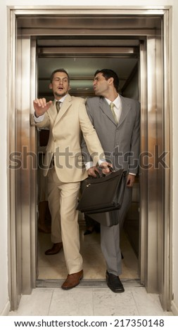 Two businessmen struggling to get out of an elevator - stock photo