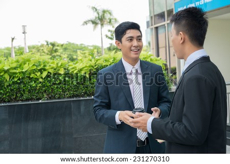 Two businessmen talking and drinking coffee outdoors - stock photo
