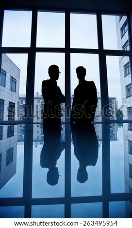 Two businessmen talking by the window in office - stock photo
