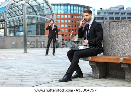 Two businessmen talking on the phone