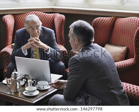 Two businessmen talking over laptop in office lobby - stock photo