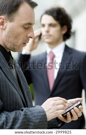 Two businessmen using different mobile devices (shallow depth of field used)