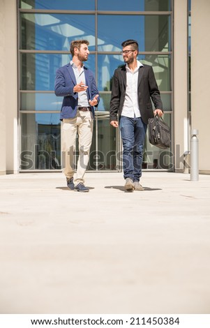 Two businessmen walking and talking outdoors - stock photo