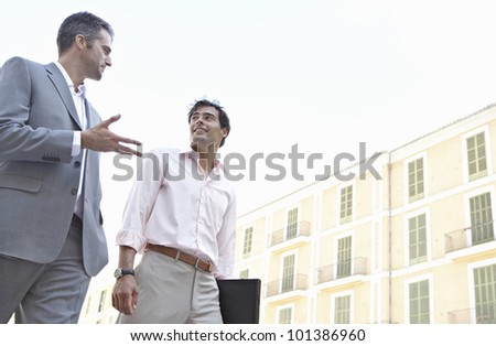 Two businessmen walking in the city and talking. - stock photo