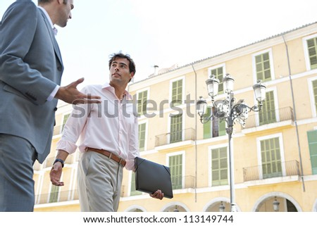 Two businessmen walking passed a building in a European city while having a conversation. - stock photo