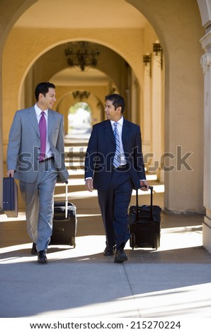 Two businessmen walking side by side in building arcade, luggage in tow, talking, front view - stock photo