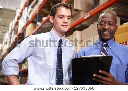 Two Businessmen With Clipboard In Warehouse - stock photo