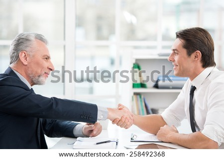 Two businessmen with documents and tablet computer. They shaking hands. Office interior with big window - stock photo