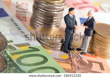 two businessmen with euro coins and euro banknotes / businessman - stock photo