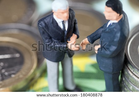 two businessmen with euro coins and euro banknotes / businessmen - stock photo