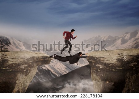 Two businessmen work together by help each other to through a gap - stock photo