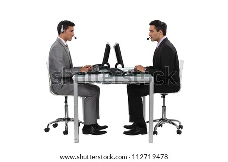 two businessmen working at the same desk