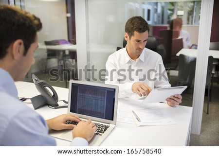 Two businessmen working in office with laptop and tablet pc - stock photo