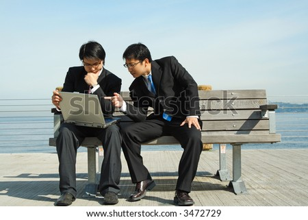 Two businessmen working together on the laptop at the seashore - stock photo