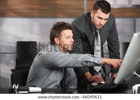 Two businessmen working together with computer at office desk, one of them pointing at screen. - stock photo