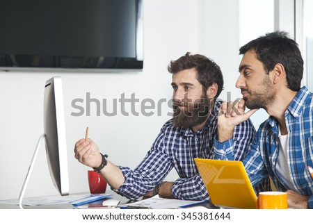 Two businessmen working with a computer in office - stock photo