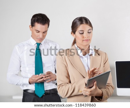 Two businesspeople checking data exchange between tablet pc and smartphone