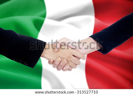 Two businesspeople closing negotiation with a good deal and shaking hands in front of italian flag background - stock photo