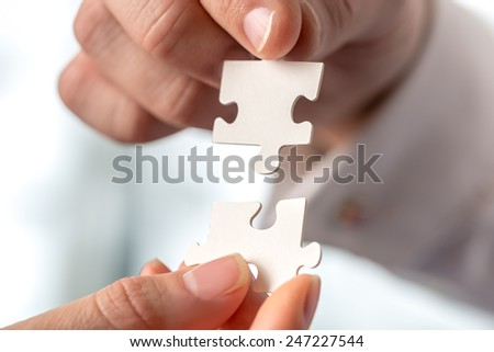 Two businesspeople fitting together matching interlocking puzzle pieces conceptual of teamwork and problem solving, closeup of their hands. - stock photo