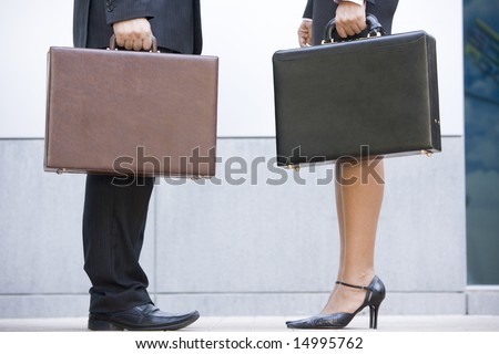 Two businesspeople holding briefcases outdoors - stock photo