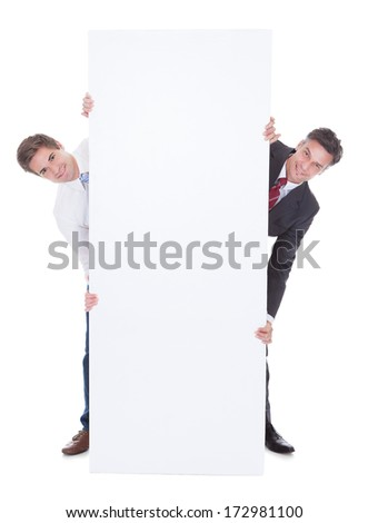 Two Businesspeople Holding White Board Over White Background - stock photo