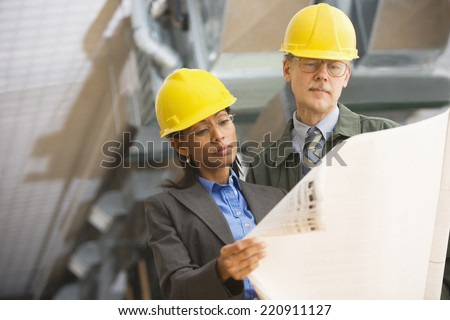 Two businesspeople in hard hats looking at blueprints