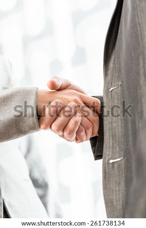 Two businesspeople in suits shaking hands over a blurred abstract background conceptual of a deal, agreement, partners or greeting, vertical format. - stock photo