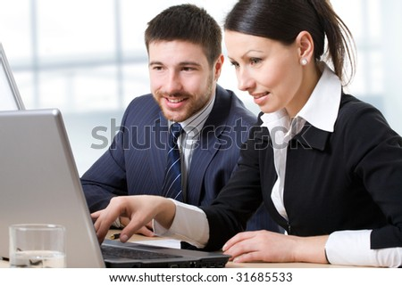 Two businesspeople looking at monitor - stock photo