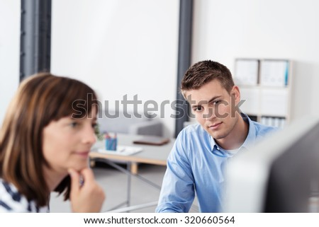 Two Businesspeople Looking at the Computer Screen Together with Serious Facial Expressions Inside the Office. - stock photo