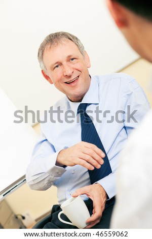Two Businesspeople - men - discussing in front of a flipchart. The mood is cheerful.