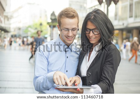Two businesspeople on street with tablet computer - stock photo