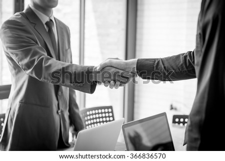 Two Businesspeople shaking hands indoors black and white tone. - stock photo