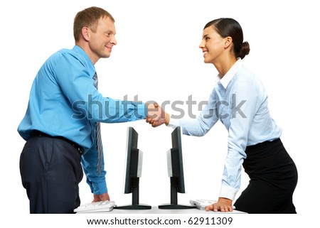 Two businesspeople shaking hands standing at two identical tables with computers - stock photo