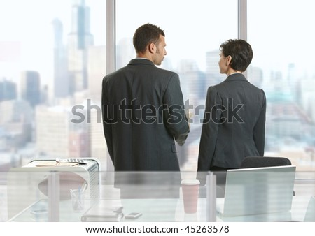 Two businesspeople standing at desk in office, looking out the windows and talking. - stock photo