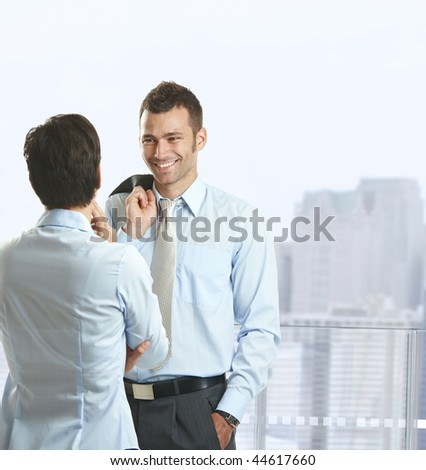 Two businesspeople standing on balcony of downtown office building, talking and smiling. - stock photo