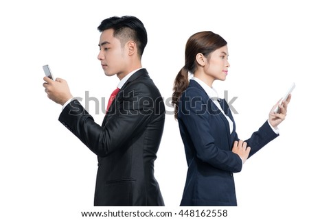 Two businesspeople standing using smart mobile phone