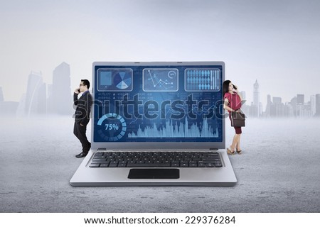 Two businesspeople talking on the phone while lean on laptop with business chart on the screen - stock photo