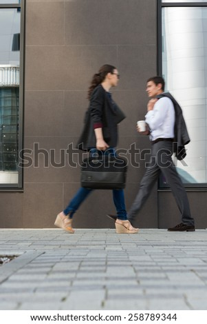 Two businesspeople walking on the street near office building