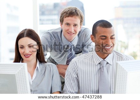 Two businesspeople working at computers with their manager in the office