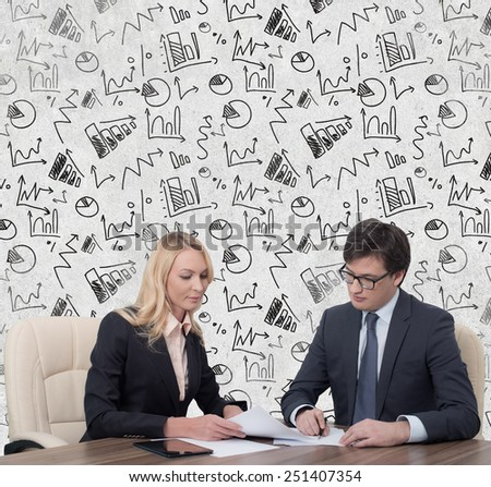 two businesspeople working in office with drawing charts on wall - stock photo