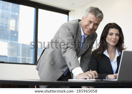 Two businesspeople working on laptop - stock photo